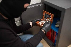 Thief stealing valuables from safe