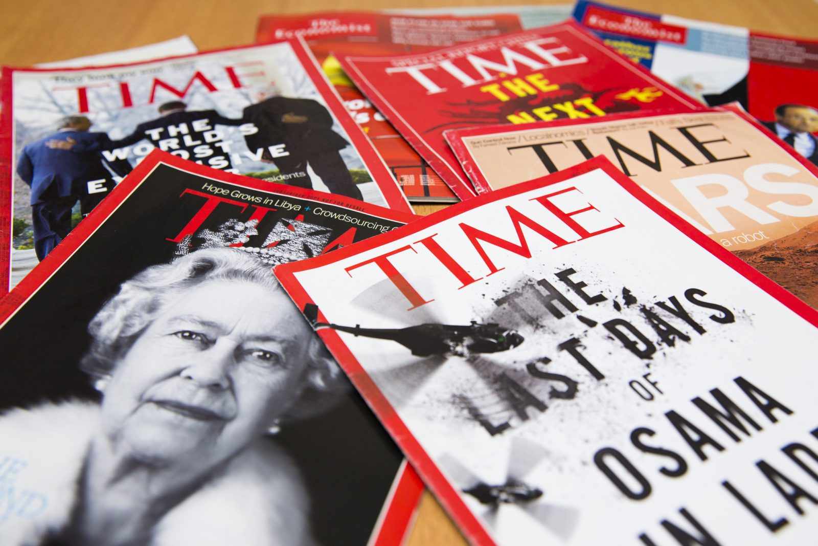 A pile of Time Magazines spread out over a table.