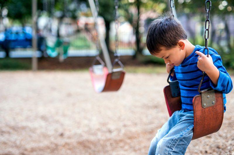 kid sad on swing