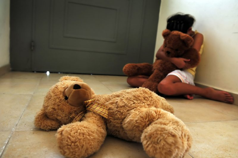 kid crying in corner bear on floor
