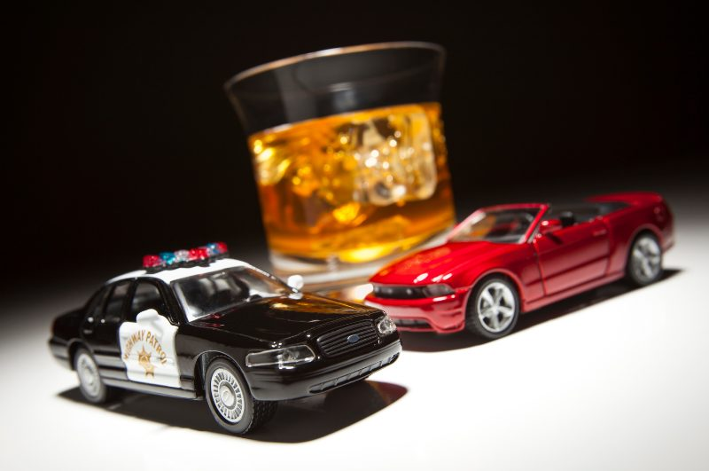 cup of whiskey with cop car and police car