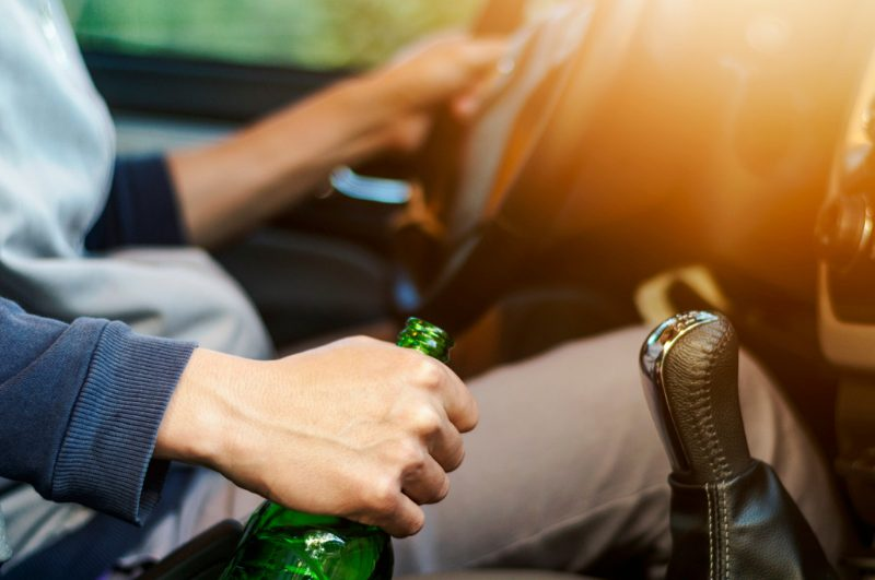 man driving with beer